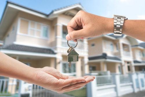 o-homem-está-entregando-uma-chave-da-casa-uma-mulher-chave-com-um-keychain-79948239